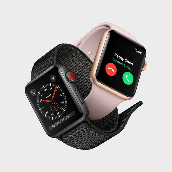 Two Apple Watch Series 3 devices interlinked by their bands.