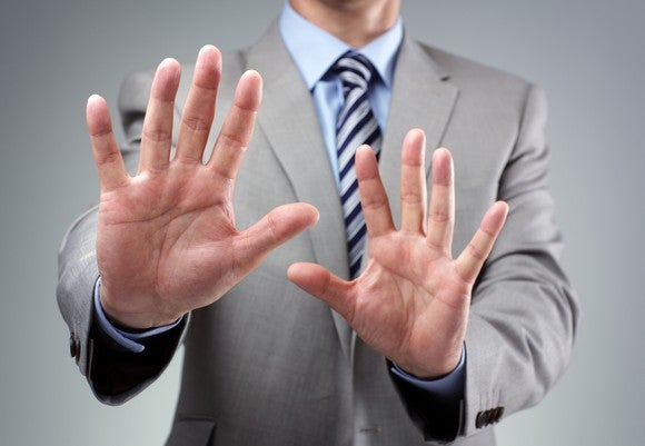 "A man in a suit putting his hands up as if to say ""no thanks."""