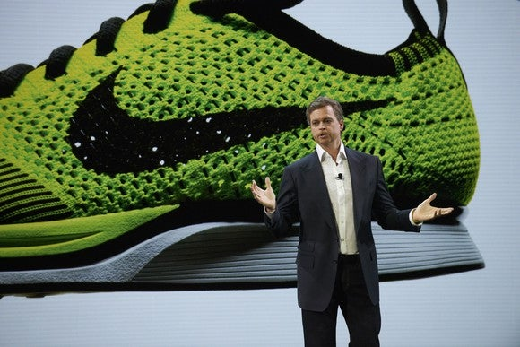 Nike CEO Mark Parker speaking with a large image of a Nike sneaker in the background.