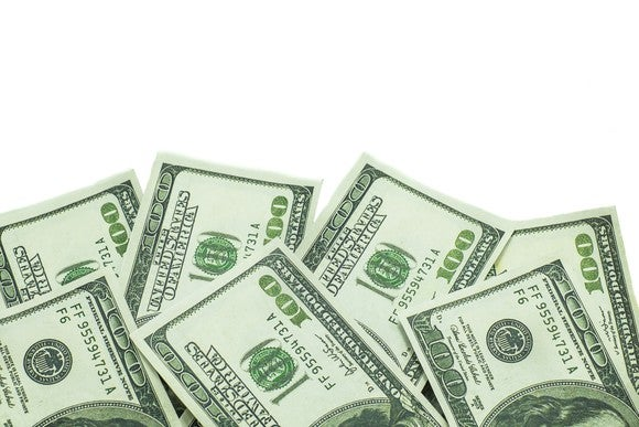 About 7 hundred dollar bills isolated on white background