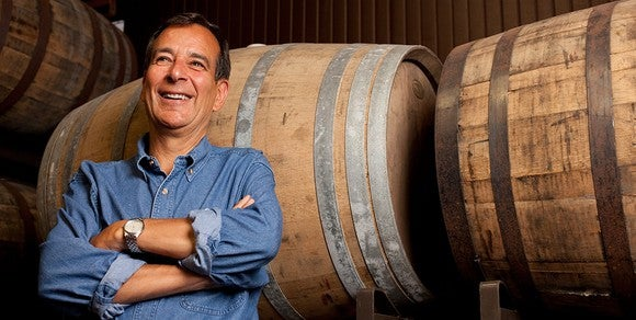 Boston Beer founder Jim Koch standing in from of some beer barrels.