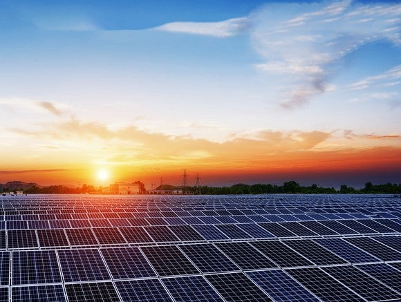 Large solar farm with a setting sun in the background.