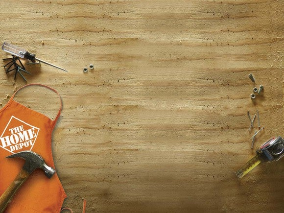 A Home Depot apron and various tools resting on a piece of wood.