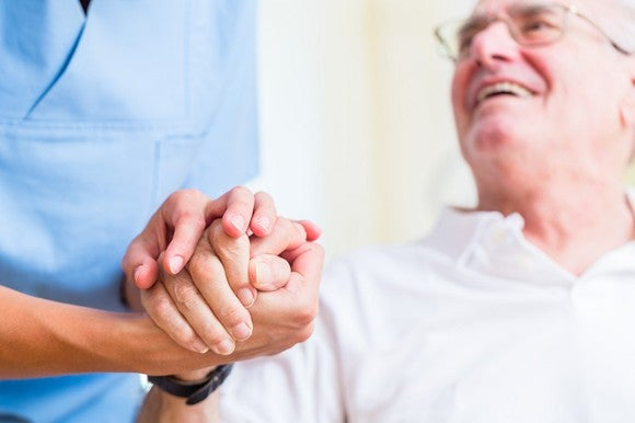 Senior man smiles up at a nurse who holds his hand.