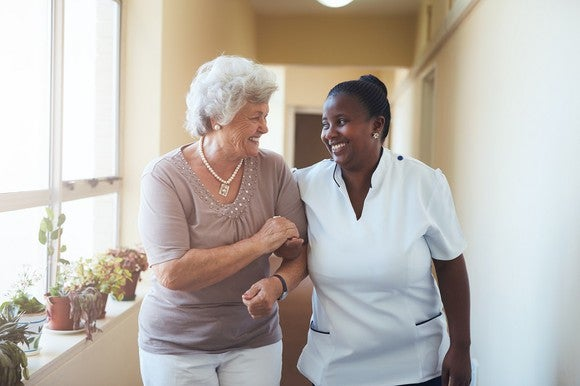 Senior woman and care attendant walk hand in hand and smile at one another.