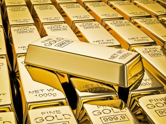 A gold bar lying atop a stack of gold bars.