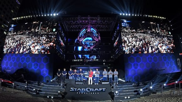 """Two teams on a stage at a competitive """"Starcraft"""" event."""