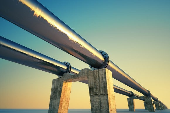 Two pipelines over water at sunset.