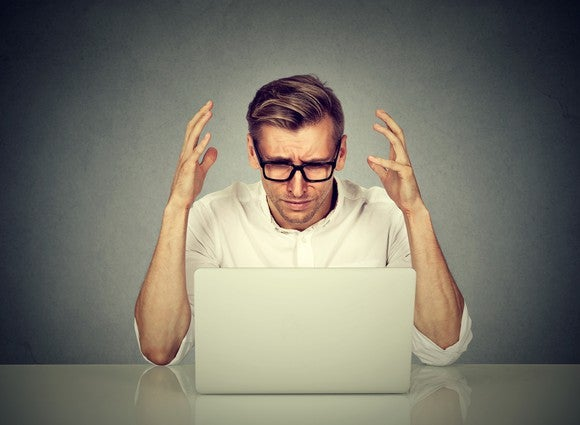 A man throws up his hands while looking at a laptop computer.