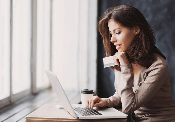 Woman using a laptop. One hand is on keyboard; other hand holds a credit card.