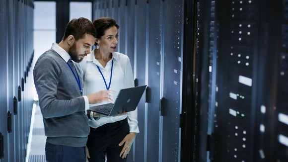 A man looks at laptop while discussing with a woman in a server room