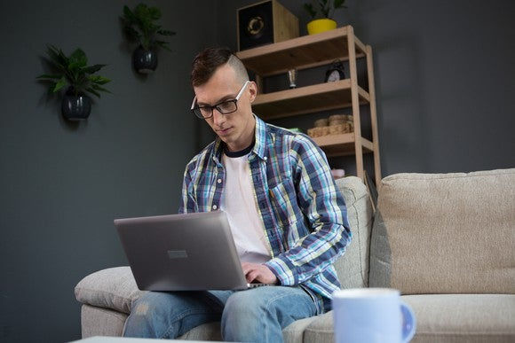 Man sitting on a couch and typing on a laptop