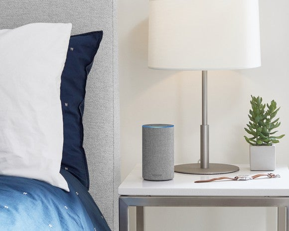 The new Amazon Echo speaker on a table next to a bed.