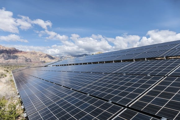 A large solar installation with mountains in the background.