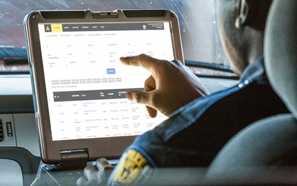 Police officer entering data into Evidence.com database