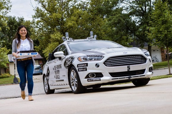 A Ford Fusion with visible self-driving sensors is in a suburban driveway. A woman holding a boxed pizza is walking away from the car.