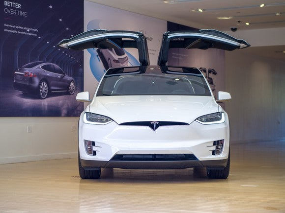 A white Model X in a Tesla store.