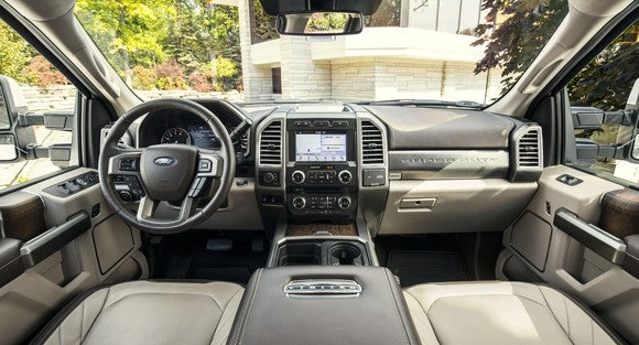 The interior of a 2018 Ford F-450 Limited, with leather seats, wood trim, and a touchscreen system visible.