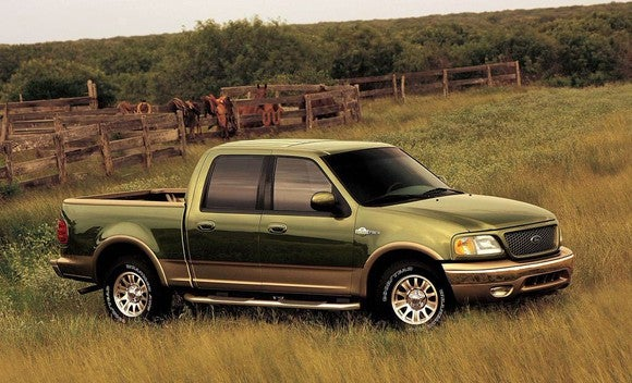 A green 2001 Ford F-150 King Ranch pickup truck in a field.
