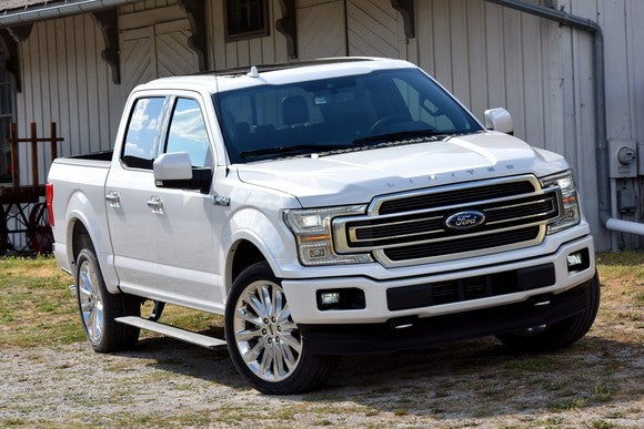 A white 2018 Ford F-150 Limited parked in front of a barn.