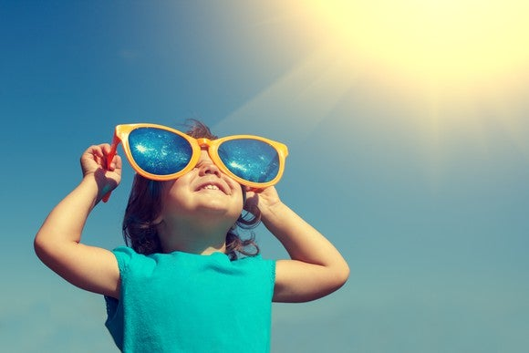 Smiling little girl wearing big sunglasses looks upward with sun in background