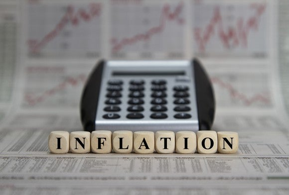 """The word """"inflation"""" spelled out with dice in front of a calculator and various rising charts in a newspaper."""