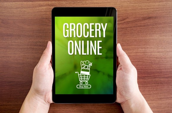 """Two hands hold a tablet showing the words """"grocery online"""" and a graphic of a filled shopping cart."""