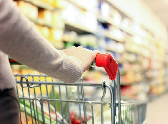 A grocery cart being pushed through a supermarket aisle.