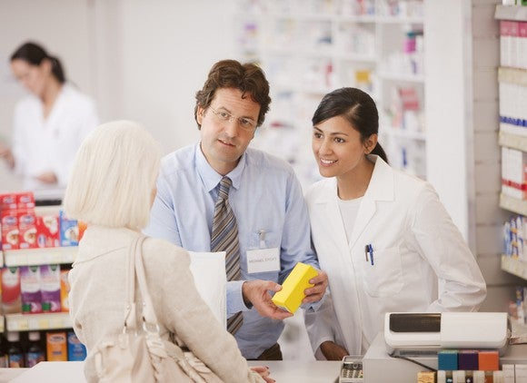 Pharmacists talking to shopper in drug store