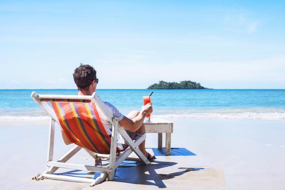 Man sitting on a beach chair facing the ocean