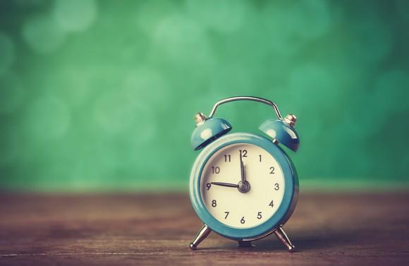 A green alarm clock on a tabletop.