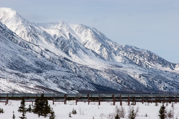 A pipeline near a snow covered mountain.