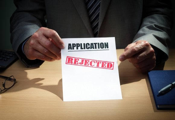 "Man in suit holding up a piece of paper that says ""Application"" with the word ""rejected"" stamped on it."