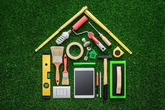 A variety of handheld home improvement tools, like paint brushes, rulers, a light bulb, and hammers, laid out neatly in the shape of a house on top of green astro turf.