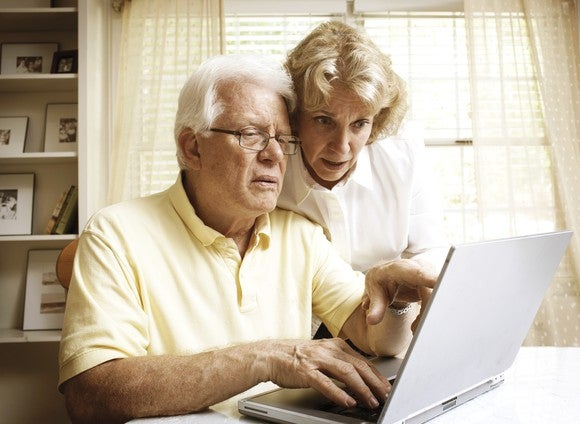 An elderly married couple reviewing their Medicare options on their laptop.