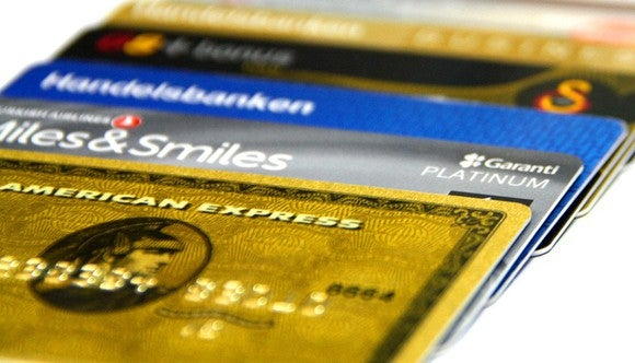A gold American Express card on top of other stacked cards.