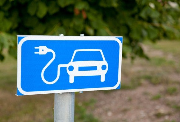 Outdoor sign with an image of a car with an electrical cord attached to it -- concept for an electric car. Sign indicates a charging station.