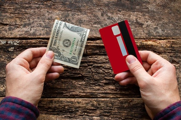 Two hands, one holding a $1 bill and the other holding a credit card.