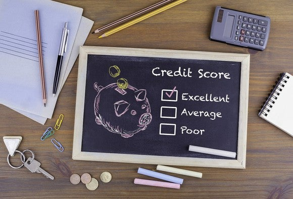 "On a desktop, surrounded by papers, pens, keys, coins, a calculator, and other items, is a small chalkboard. Drawn on the chalkboard is a picture of a piggy bank, next to the words ""credit score."" Beneath that are written ""excellent,"" ""average,"" and ""poor,"" with check boxes next to each. The box next to ""excellent"" is checked."