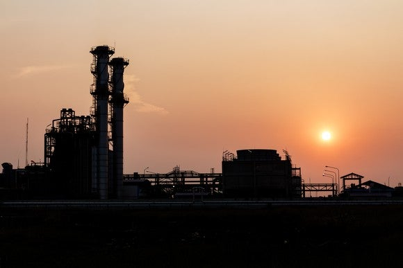 A refinery tower at sunset.