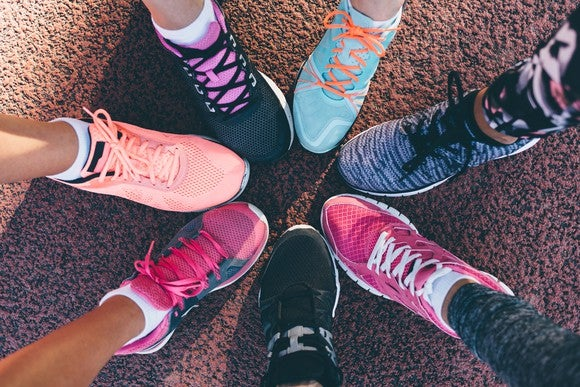 Seven people's legs arrange in a circle to show off their athletic shoes