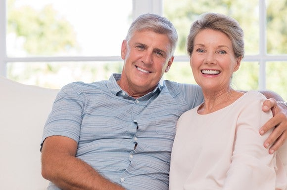 A smiling older man sits on a sofa next to a smiling older woman, with an arm around her shoulder.