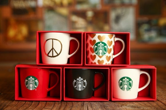Five Starbucls mugs stacked in two rows.