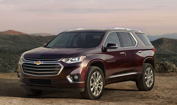 A wine-red 2018 Chevrolet Traverse crossover SUV parked with mountains in the background.