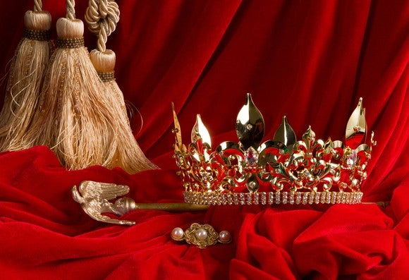 A crown and scepter arranged on red velvet.