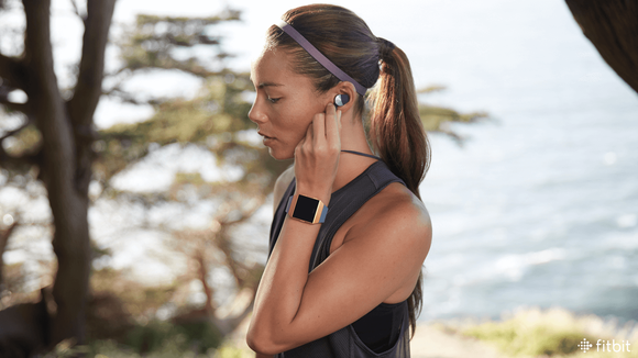 A jogger wearing an Ionic smartwatch and Fitbit Flyer headphones.