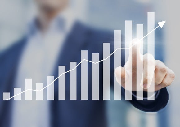 A businessman touching a screen with a bar chart on it showing growth.
