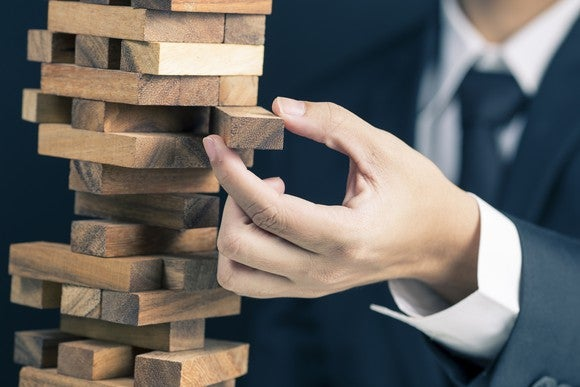 A man in a suit pulling a block from a Jenga-type tower