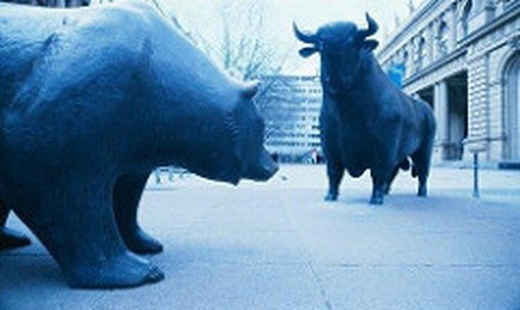 Blue-tint photo of statues of a bull and a bear arranged so as they are facing off against one another, with urban buildings in the background.