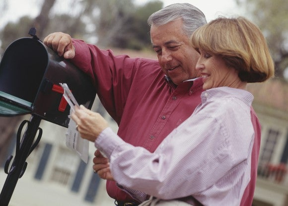 Middle-aged couple checking mail at a mailbox